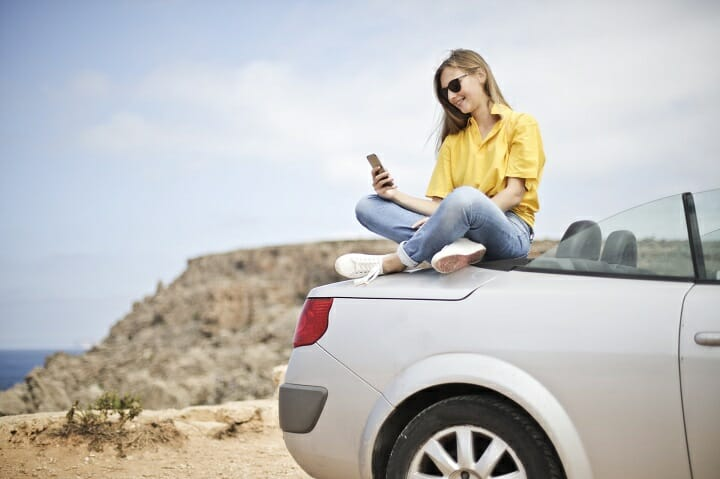 A woman sitting on the back of a convertible - Young drivers will pay more for insurance