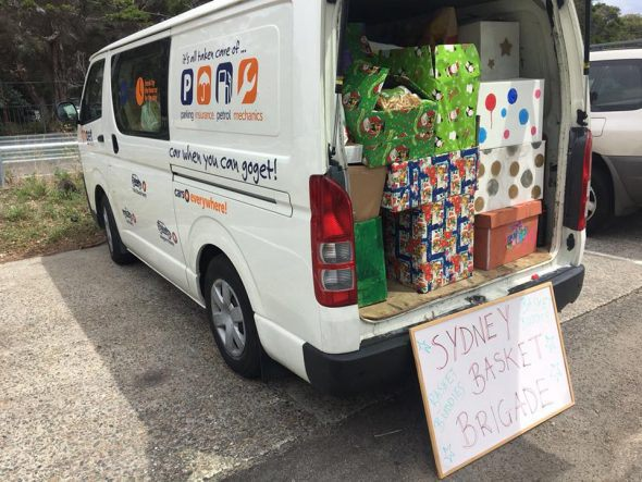 A side shot of a GoGet van chock full of Christmas Presents, a sign reads Sydney Basket Brigade. Sydney Basket Brigade used GoGet vans to pickup and deliver Christmas presents to the needy at Christmas.