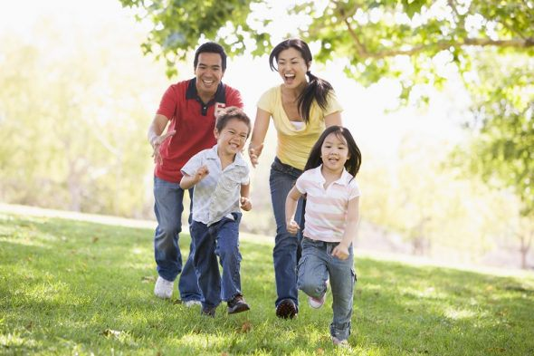 A family running outdoors smiling. School Holiday activities are always important to organise ahead of time