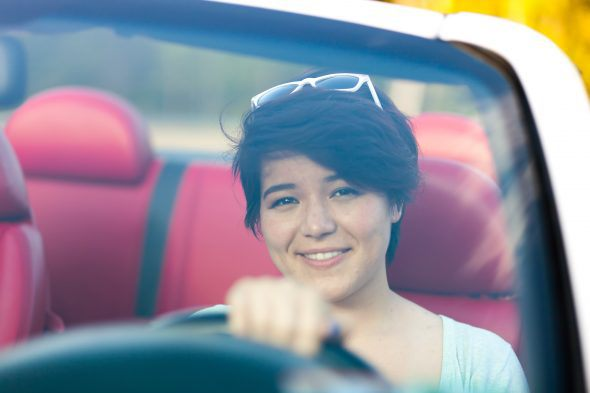 A female young driver smiling in a convertible sports car with red leather interior. Shallow depth of field.