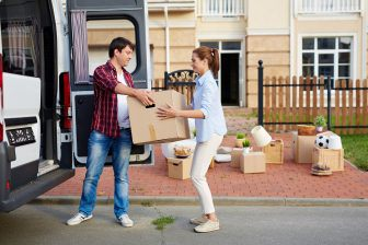 A couple is moving house, unpacking boxes from their van